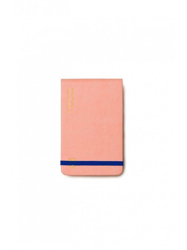 rožinė užrašų knygelė saulės metai baltame fone
